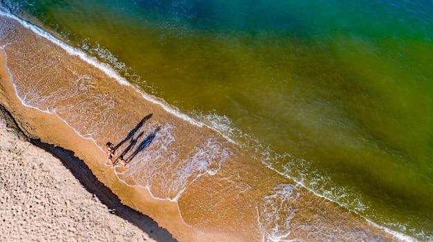 Mamãe e filhas caminham pelas ondas à beira-mar