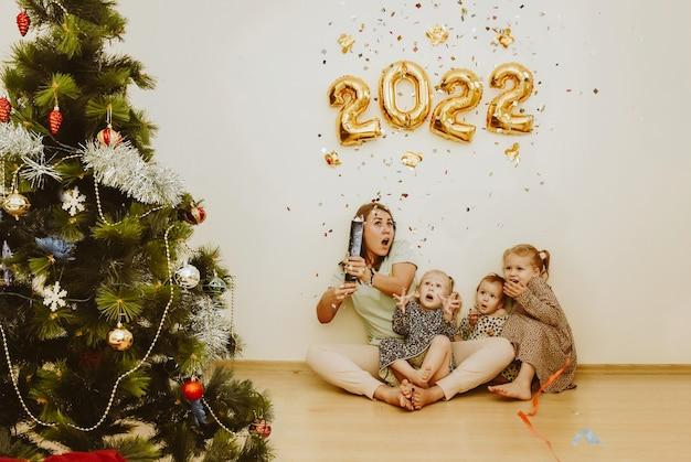 Mamãe e filhas com verdadeiras emoções de alegria explodem um badalo de confete no ano novo