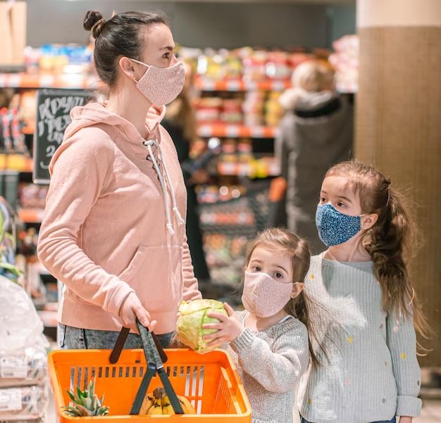 Mamãe e filhas compram máscaras na loja durante a quarentena devido à pandemia de coronavírus.