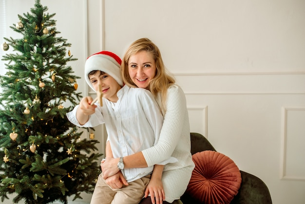 Mamãe e herson brincam deitados na sala de natal. eles decoram uma árvore de natal de madeira com luzes