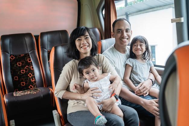 Mamãe e papai asiáticos sorriem para a câmera enquanto pegam seus dois filhos sentados no banco do ônibus durante a viagem