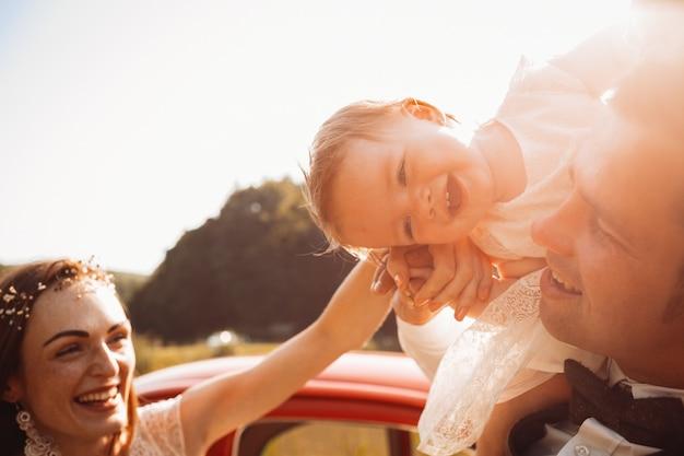 Mamãe e papai brincam com sua filha antes de um carro vermelho