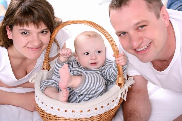 Mamãe e papai colocam uma criança pequena em uma cesta.