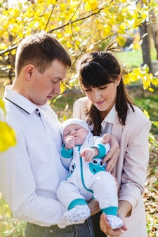 Mamãe e papai com um bebê, um garotinho andando no outono no parque ou na floresta. folhas amarelas, a beleza da natureza. comunicação entre um filho e um pai.