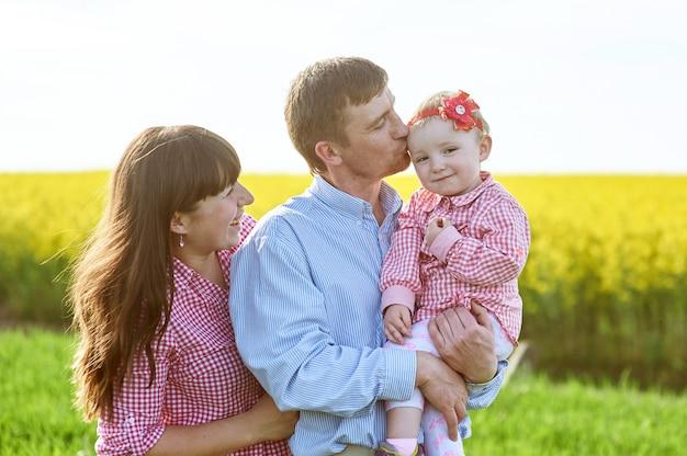 Mamãe e papai e filha estão andando no campo verde verão