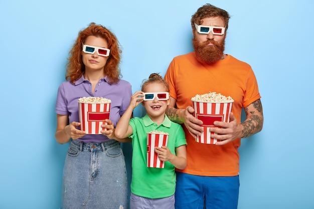Mamãe e papai entediados ficam indiferentes enquanto a filha assiste desenhos animados interessantes no cinema, usa óculos tridimensionais, roupas de verão casuais brilhantes, passa o tempo livre para se divertir