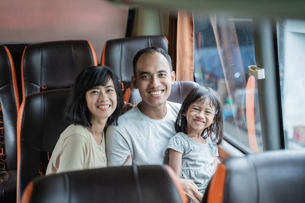 Mamãe e papai sorriem para a câmera enquanto dão colo nas filhas enquanto se sentam nos assentos do ônibus no caminho
