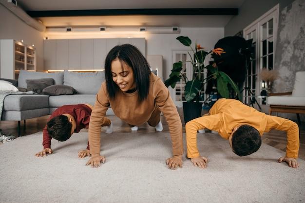 Mamãe ensina seus dois filhos a praticar exercícios físicos esportivos pela manhã em casa