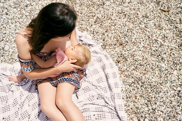 Mamãe está amamentando uma menina em uma vista superior de uma praia de seixos