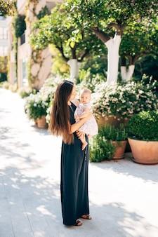 Mamãe está com uma menina com um vestido nos braços, perto de banheiras com arbustos verdes