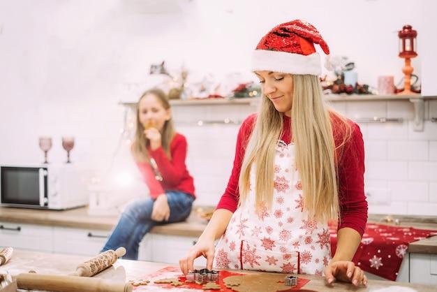 Mamãe está na cozinha de avental e suéter vermelho, fazendo biscoitos de gengibre