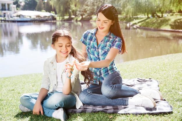 Mamãe está sentada atrás da filha e trança o cabelo. ela está tomando um elástico da criança. menina está sentada e segurando alguns elásticos no dedo. ela está sorrindo.