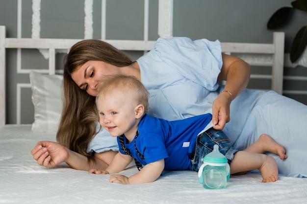 Mamãe feliz brincando na cama com um menino