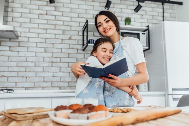Mamãe fica com o livro de receitas e preparando comida com a filha