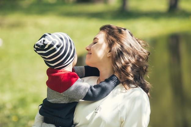 Mamãe gentilmente abraça seu filho. mãe caminha com o filho no parque no verão.
