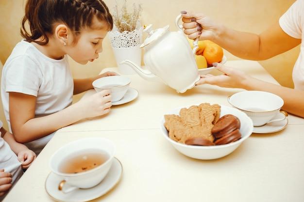 Mamãe jovem e bonita na cozinha com seus filhos bebendo chá com biscoitos