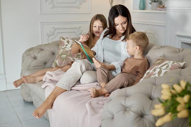 Mamãe lê um livro para as crianças. uma mulher conta uma história para um menino e uma menina antes de ir para a cama. filha mãe e filho relaxam em casa em um dia de folga
