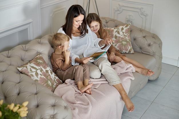 Mamãe lê um livro para as crianças. uma mulher conta uma história para um menino e uma menina antes de ir para a cama