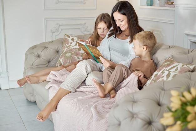 Mamãe lê um livro para as crianças.