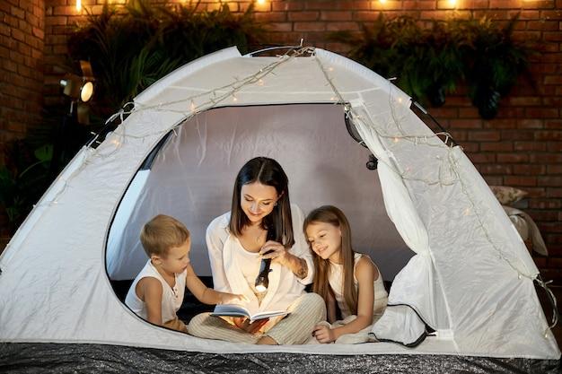 Mamãe lê uma história para as crianças antes de dormir, sentada em uma barraca em casa