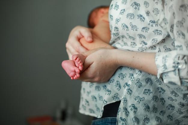 Mamãe mantém o bebê recém-nascido. mamãe amamenta bebê. mamãe gentilmente abraça o bebê