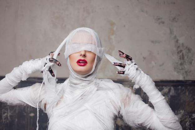Mamãe menina de olhos vendados. retrato de uma jovem mulher bonita em bandagens por todo o corpo.