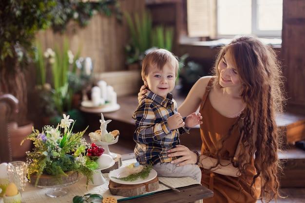 Mamãe mostra o filho de uma pequena galinha recém-nascida. o garoto beija a garota com ternura e charme. todler em uma fazenda na zona rural. ovos de celebração do conceito de páscoa decoração de mesa. primavera natureza eco veg