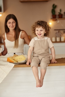 Mamãe observa enquanto seu filho se senta à mesa e come queijo.