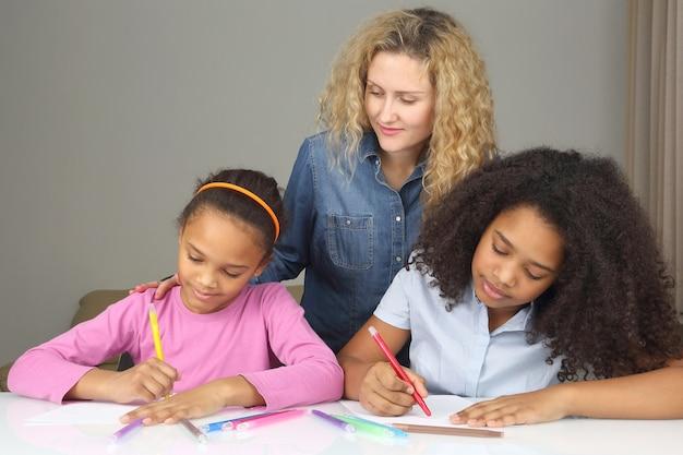 Mamãe observa sua filha desenhando com giz de cera