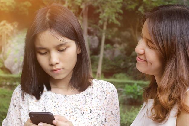 Mamãe olha para uma filha adolescente que leva a sério o uso de um smartphone.