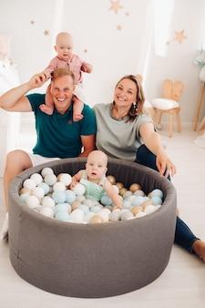 Mamãe, papai e dois filhos caucasianos se divertem juntos e sorriem