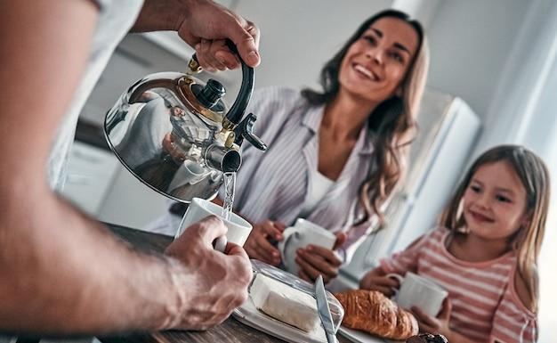 Mamãe, papai e sua linda filha fazem uma festa do chá na cozinha e conversam. conceito de família feliz.