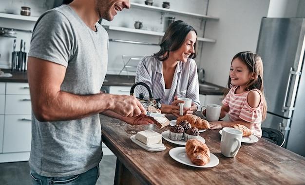 Mamãe, papai e sua linda filha fazem uma festa do chá na cozinha e conversam. o pai põe manteiga no pão. conceito de família feliz.