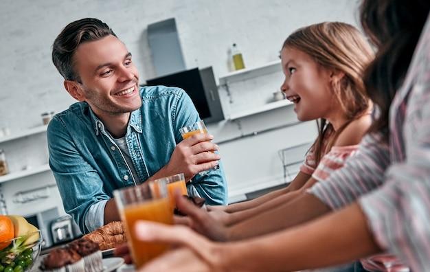 Mamãe, papai e sua linda filha tomam café da manhã na cozinha e conversam. conceito de família feliz.