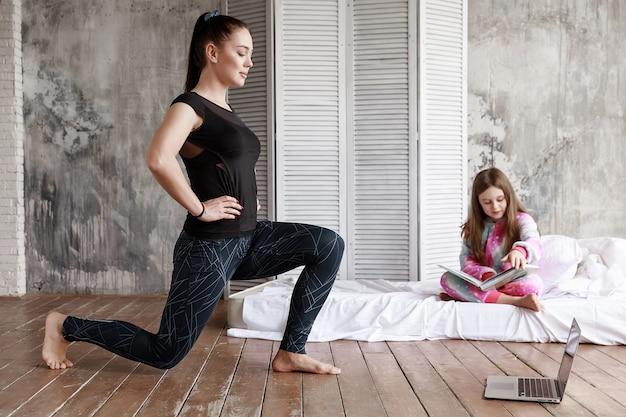Mamãe pratica esportes em casa, cem aulas on-line e minha filha está sentada ao lado dela lendo um livro