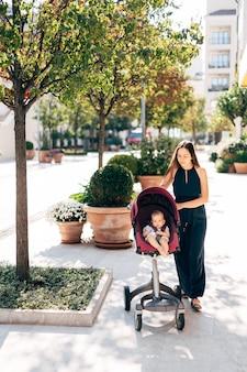 Mamãe rola o carrinho com o bebê pelas banheiras com arbustos verdes