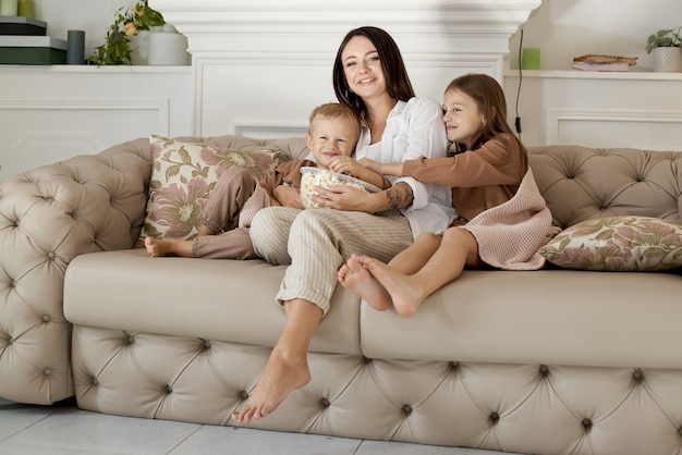 Mamãe se senta no sofá com seu filho e filha e assiste a um filme. uma mulher, um menino e uma menina comem pipoca enquanto assistem a um filme. a família está descansando em casa no fim de semana
