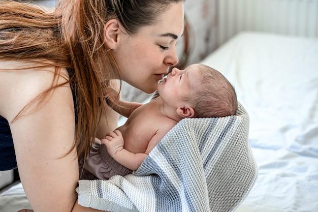 Mamãe segura um menino recém-nascido enrolado em um cobertor nos braços e beija.