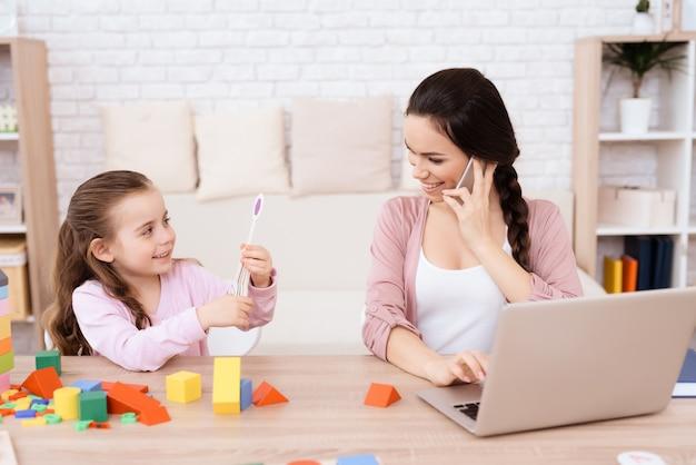 Mamãe senta e fala ao telefone ao lado de sua filha.
