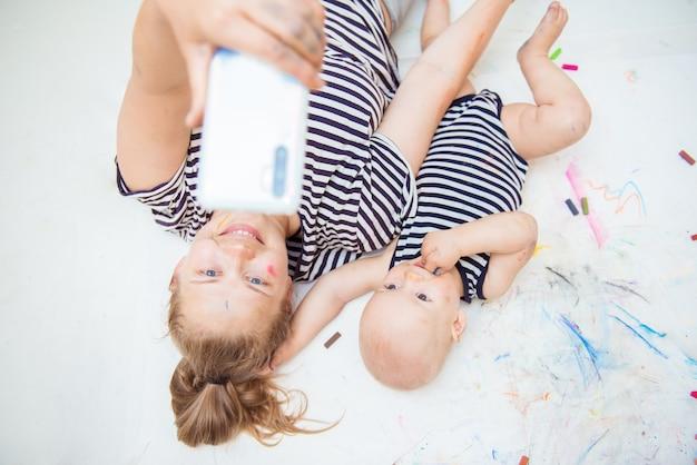 Mamãe tira uma selfie com seu bebê depois de desenhar com giz de cera colorido. o conceito de desenvolvimento inicial da criatividade das crianças