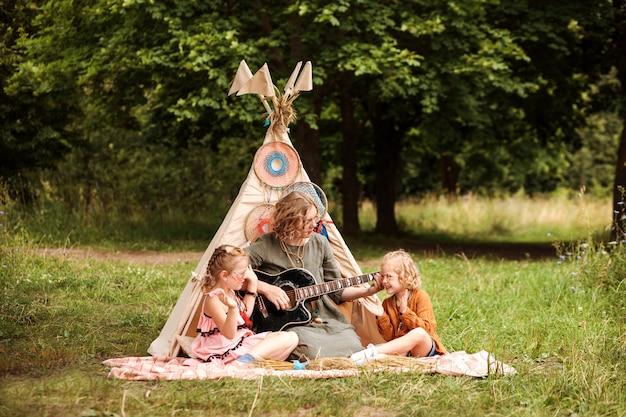 Mamãe toca violão para sua filha sentada ao lado da cabana na floresta.