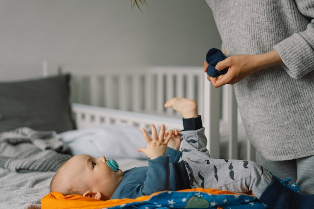 Mamãe veste um lindo garotinho com um macacão. feliz jovem mãe brincando com o bebê na cama. feliz maternidade. bebê infantil.