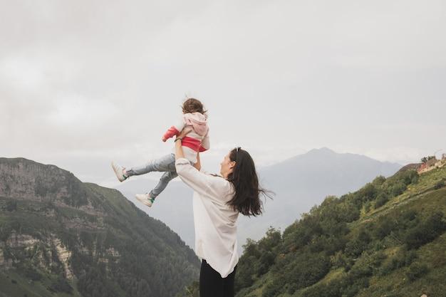Mamãe viaja pelas montanhas com seu filho pequeno, a mãe joga o filho e pega o bebê com pa ...