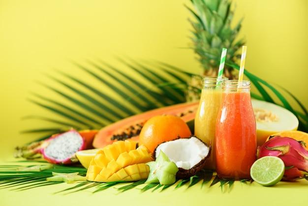 Mamão e abacaxi suculentos, manga, batido de fruta alaranjado em dois frascos. desintoxicação, alimento da dieta do verão, conceito do vegetariano.