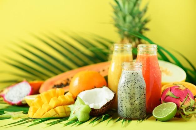Mamão e abacaxi suculentos, manga, batido de fruta alaranjado em uns frascos no fundo amarelo. desintoxicação, alimento da dieta do verão, conceito do vegetariano.