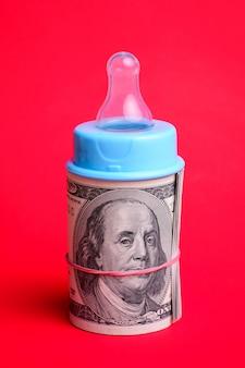 Mamilo de mamadeira em um rolo de dinheiro dólar