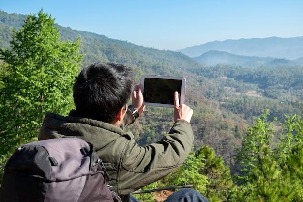 Man traveler com câmera de tablet e mochila caminhadas ao ar livre travel lifestyle and adventure concept.
