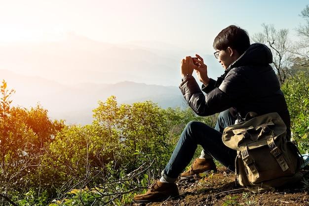 Man traveler com câmera de telefone inteligente e mochila caminhando ao ar livre travel lifestyle and adventure concept.