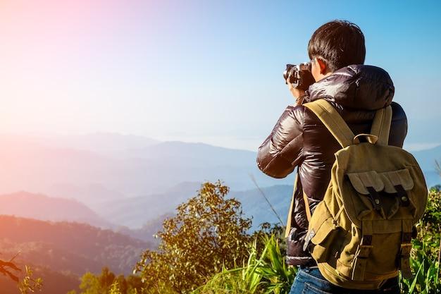 Man traveler com câmera fotográfica e mochila caminhadas ao ar livre travel lifestyle and adventure concept.