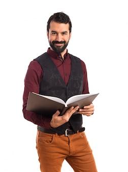 Man usando livro de leitura de colete